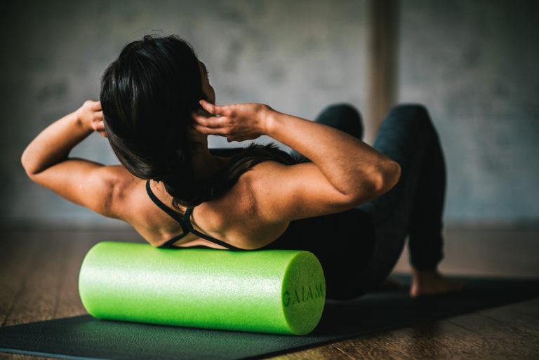a woman exercises with a green foam roller