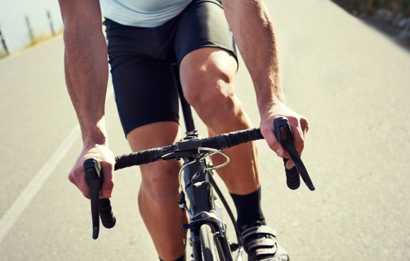 Cropped shot of a sportsman cycling on a road with a scenic view