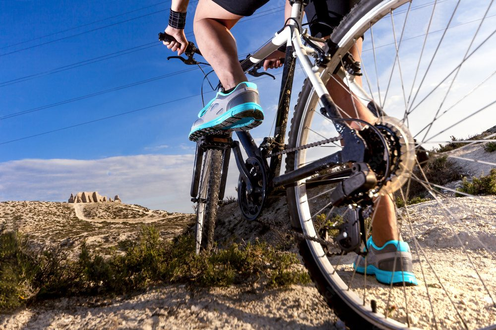 The man's foot with a bicycle outdoor cycling interval training