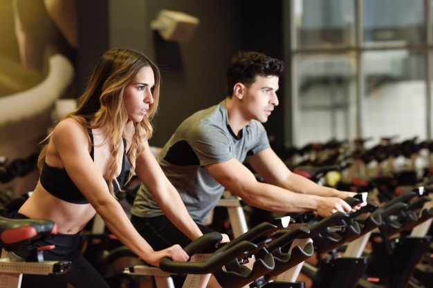boy and girl do indoor cycling